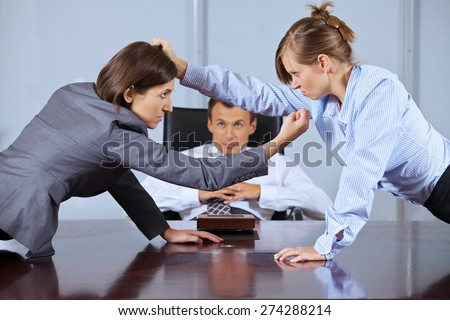 Businesswomen arguing in front of businessman at office - stock photo