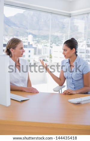 Businesswomen arguing in the office sitting at their desk - stock photo