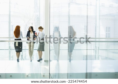 Businesswomen conversing at office hallway - stock photo