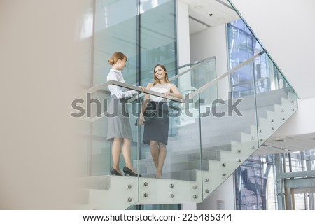 Businesswomen conversing on steps in office - stock photo