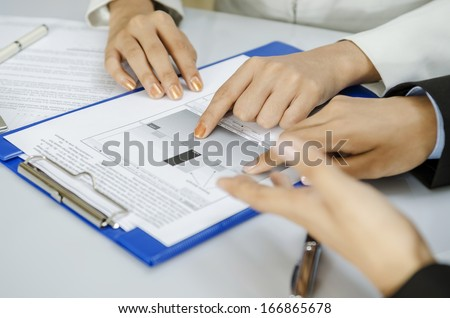Businesswomen discussing on printout in office