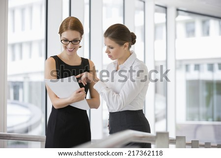 Businesswomen discussing over documents in office - stock photo