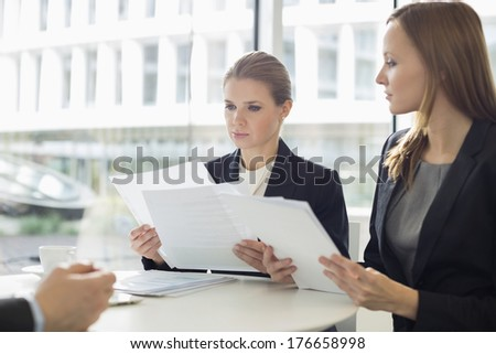 Businesswomen discussing over documents in office cafeteria - stock photo