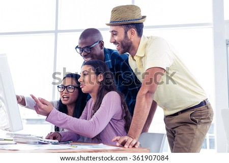 Businesswomen explaining colleagues over computer at creative office - stock photo