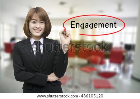 Businesswomen hand writing engagement with black marker on visual screen. Isolated on background. Business, technology, internet concept. - stock photo