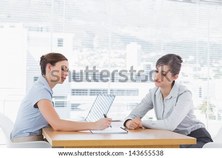 Businesswomen having a meeting at desk in an office - stock photo