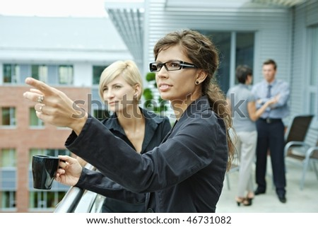 Businesswomen having break on office terrace outdoor drinking coffee. - stock photo