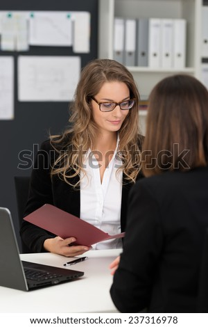 Businesswomen in Black and White Business Suits Having Business Meeting at White Table with Laptop Computer. - stock photo