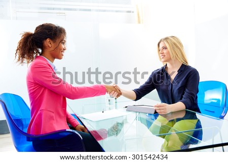 businesswomen interview handshake multi ethnic african and blond sitting at office - stock photo