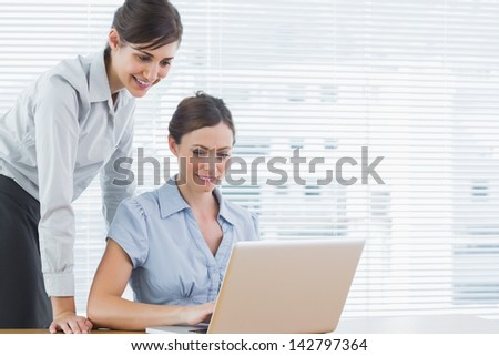 Businesswomen looking at a laptop together at desk in office - stock photo
