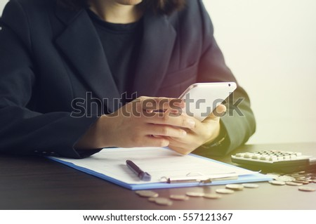 businesswomen press phone on with document of finance, coins and calculator on desk