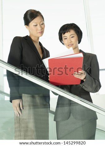 Businesswomen reviewing documents while standing on stairs - stock photo
