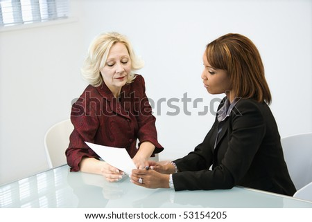 Businesswomen sitting at office desk discussing paperwork. - stock photo