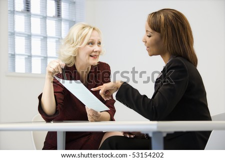 Businesswomen sitting at office desk going over paperwork pointing and smiling.