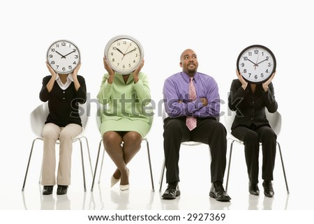 Businesswomen sitting holding clocks over faces while African-American businessman looks on.