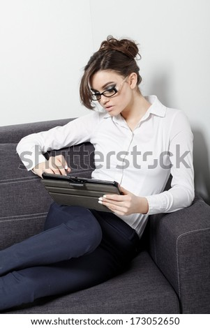 Businesswomen sitting on couch with digital tablet and studying at home
