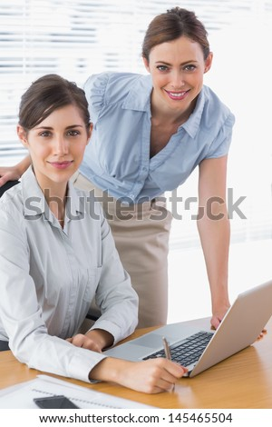 Businesswomen smiling at camera at desk with laptop - stock photo
