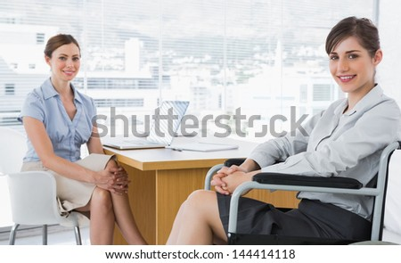 Businesswomen smiling at camera with one sitting in wheelchair in an office - stock photo