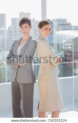 Businesswomen standing back to back and smiling in bright office - stock photo