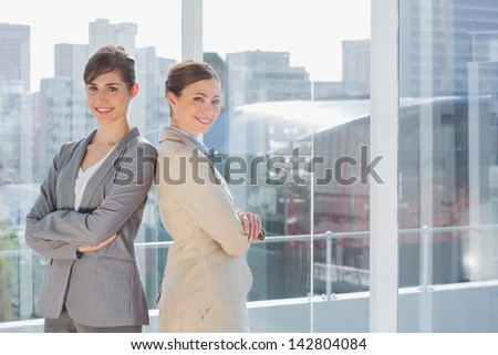 Businesswomen standing back to back in bright office - stock photo