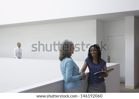 Businesswomen talking in office hallway with male colleague in background - stock photo