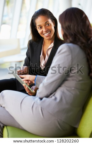 Businesswomen With Digital Tablet Sitting In Modern Office - stock photo