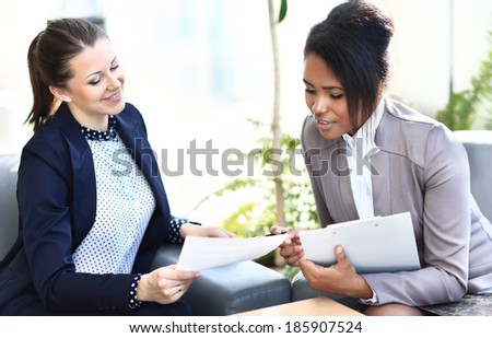 Businesswomen With documents and folder Sitting In Modern Office and discuss business matters