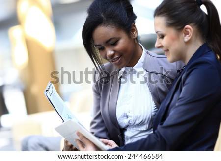 Businesswomen With documents and folder Sitting In Modern Office and discuss business matters - stock photo