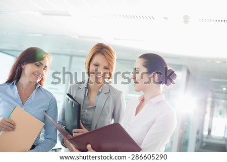 Businesswomen with file folders discussing in office - stock photo