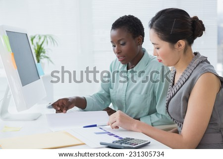 Businesswomen working together at desk in creative office - stock photo