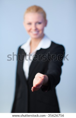 Busineswwoman offering a handshake to the camera - stock photo