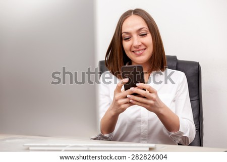 Businneswoman is writing an email from her mobile phone in office - stock photo