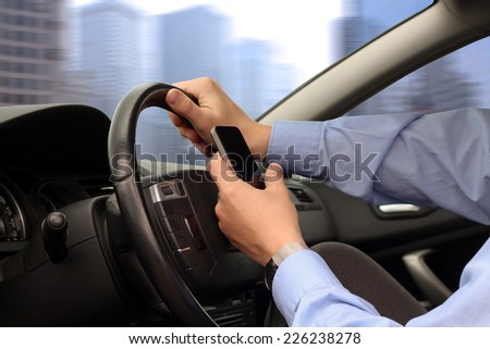 businwssman using  mobile smart phone while driving the car - stock photo