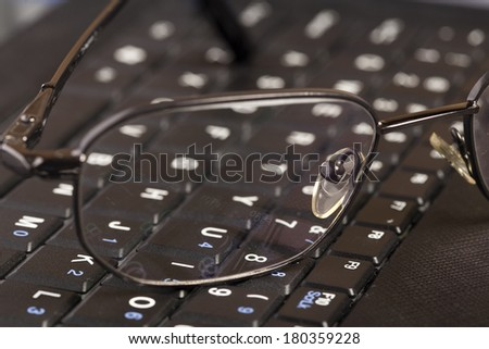 Bussines concept. Glasses on the keyboard - stock photo