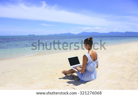 Bussines woman working on the beach with a laptop, she is a freelancer