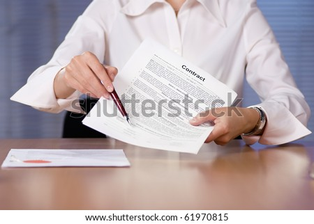 Bussinesswoman (or notary public) holding pen pointing at signature place on a contract document