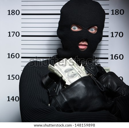 Busted burglar. Angry burglar holding a bag with stolen goods while standing against police line-up - stock photo