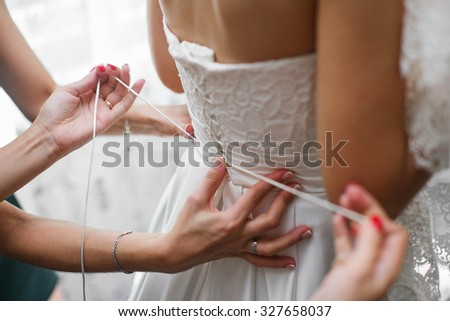 Bustling a Wedding White Dress and hands