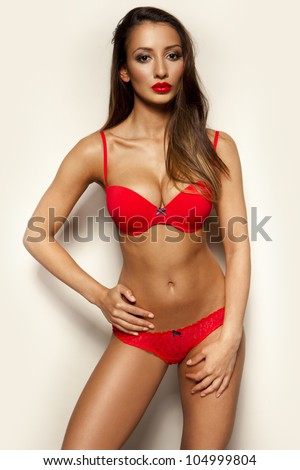 Busty dark skinned beauty with a sultry look and large breasts posing in red lingerie - stock photo