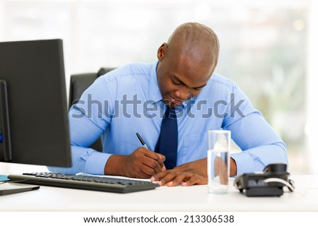 busy afro american businessman working in office - stock photo