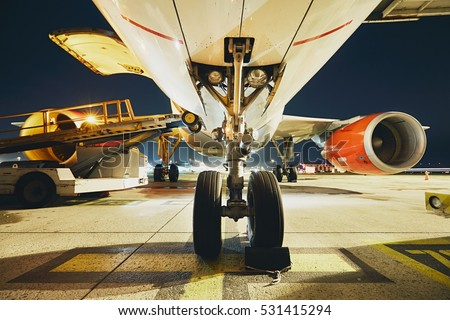 Busy airport in the night. Preparation of the airplane before flight.