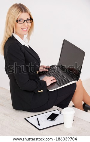 Busy and confident. Top view of confident mature businesswoman looking over shoulder and smiling while sitting at the staircase and working on laptop - stock photo