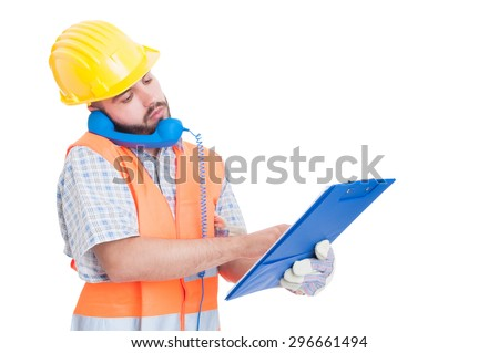 Busy builder using phone while holding clipboard. Support or assistance for construction company - stock photo