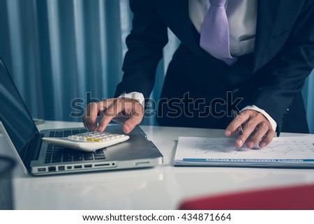 Busy business man quickly working financial reporting assests data in the business office workplace, he is calculate business busines gross profit value for the purpose of meeting. - stock photo