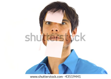 Busy business man with post it notes all over his face isolated over a white background - stock photo