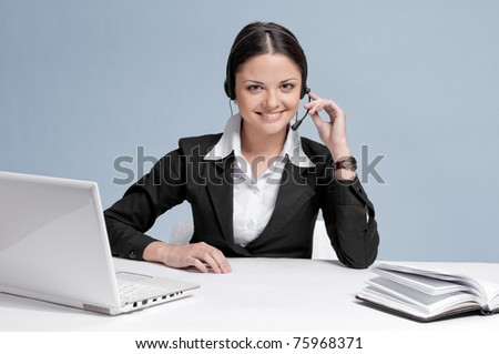 Busy business woman in office place talking by wireless headset over white table, laptop and diary. Smile!