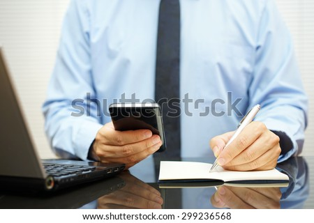 busy businessman at  office desk is using smart mobile phone, writing in notebook and watching computer screen - stock photo