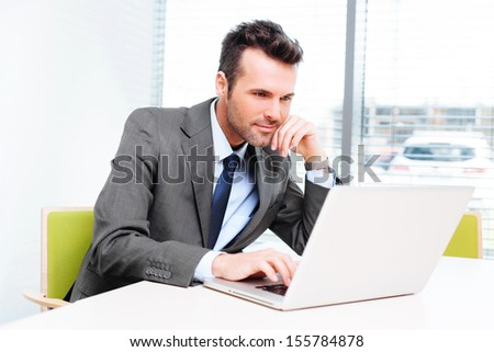 Busy businessman in office working on his laptop. - stock photo