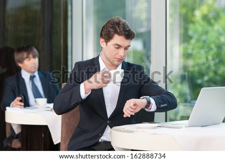 Busy businessman is looking at watch. While drinking coffee  - stock photo