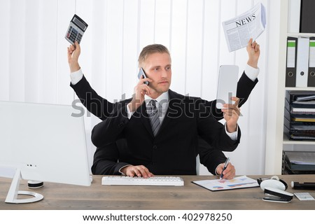 Busy Businessman Multitasking At Desk In Office - stock photo